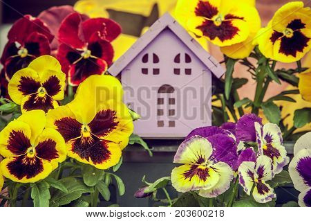 Toy house with a sun on a beautiful background. Symbol of happiness, family and peace.Theme of happiness, warmth, good luck,   love, construction, travel, hotel business, family