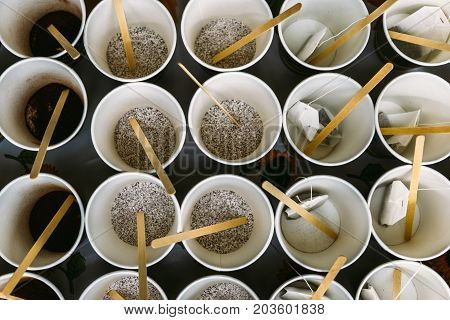Paper disposable cups with tea bags and instant coffee, top view