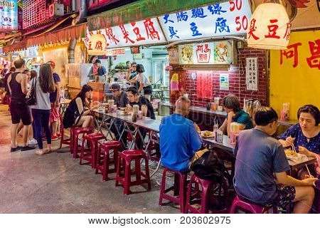 TAIPEI TAIWAN - JULY 02: This is a night scene of Jingmei night market where many local Taiwanese people come at night to eat various types of Taiwanese food on July 02 2017 in Taipei