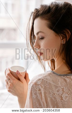 Sensual young woman with cup of coffee in front of window. Advertizing of every morning practice to drink favorite aromatic beverage. Thoughtfulness, calmness and romantic concept, close up
