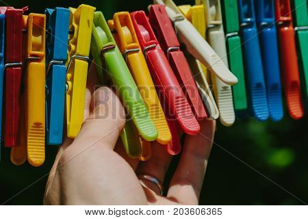 Group of colored clothespins that a man holds. Photo in the daytime.