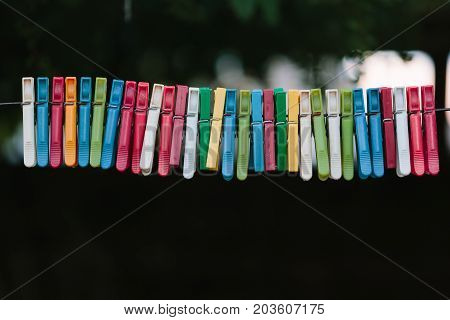 Colorful group of clothespins on a rope. On a black background.