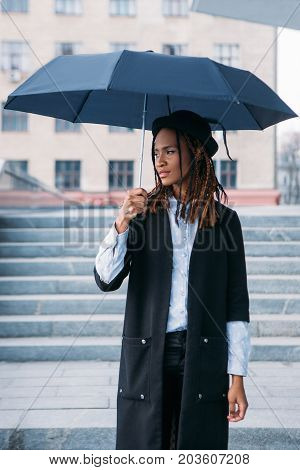 Fashion female model with an umbrella outdoors. Moody weather. Thoughtful black woman on rainy day in selective focus, style concept