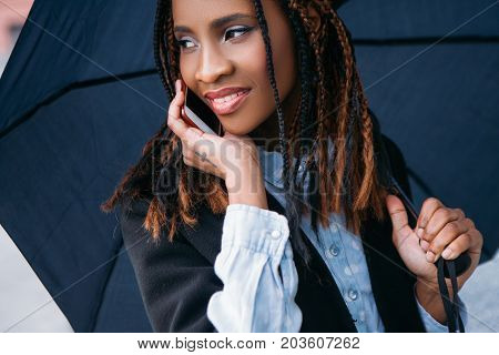 Modern social communication. Happy conversation. Moody weather, joyful black female with an umbrella on rainy day, happiness concept