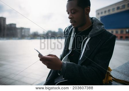 Social media communication. Pensive black man chatting on smartphone. Modern lifestyle, street style, young male in selective focus, technology concept
