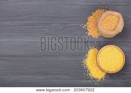 Millet in a wooden bowl, burlap bag and green spikelets on the black wooden background with copy space for your text. Top view.