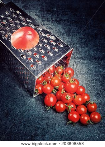 Culinary concept. Still life. Kitchen accessory. Preparation recipe tomato juice. Large tomato and old grater down to small grape cherry tomatoes on retro vintage rustic gray stone background. Low calorie food.