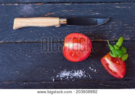 Knife With A Wooden Handle And A Black Blade. Sliced Red Tomatoes On A Black Background.