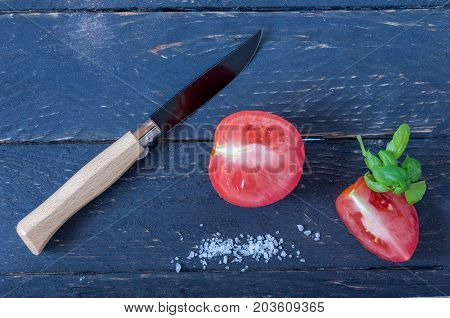 Knife With A Wooden Handle And A Black Blade. Sliced Tomatoes.