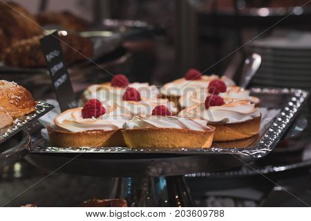 Cakes with whipped cream and raspberries in a pastry shop.