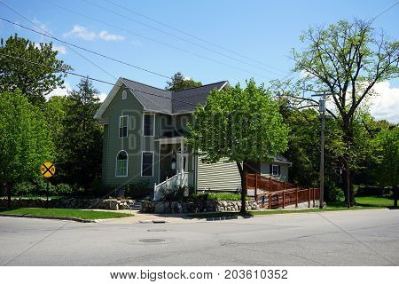 A two story single family green home, with a ramp, near railroad tracks, in Petoskey, Michigan, during May.