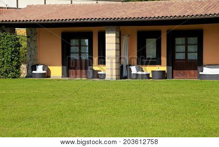 Small villa with terrace and green grass in summer village, Italy