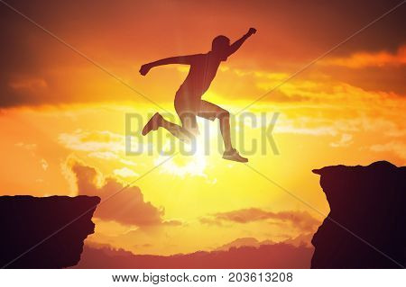 Silhouette Of Man Jumping Over A Gap At Sunset.
