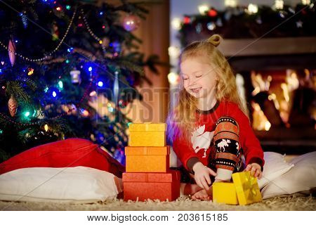 Happy Little Girl Wearing Christmas Pyjamas Playing By A Fireplace In A Cozy Dark Living Room On Chr