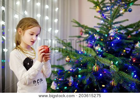 Adorable Little Girl Decorating The Christmas Tree With Colorful Glass Baubles. Trimming The Christm