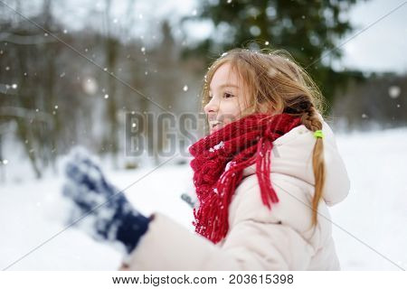 Adorable Little Girl Having Fun In Beautiful Winter Park. Cute Child Playing In A Snow.
