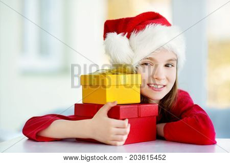 Adorable little girl wearing Santa hat opening a giftbox on Christmas morning. Celebrating Xmas at home.