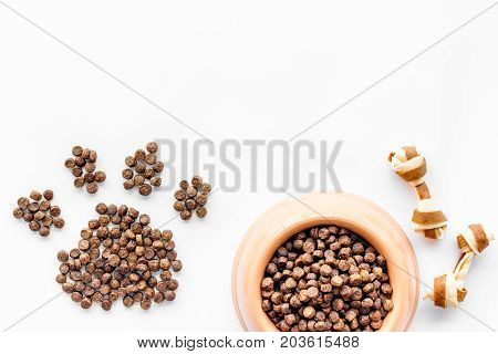pet care with dry food for pet - dog in plastic bowl and paw print on white desk background top view space for text