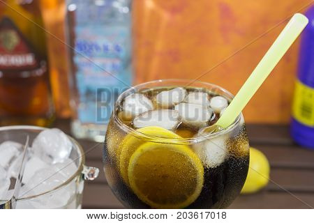 Cuba Libre Cocktail in a glass with ice and lemon