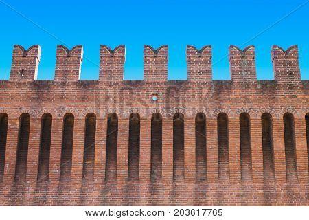 Italian medieval wall in red bricks seen from below