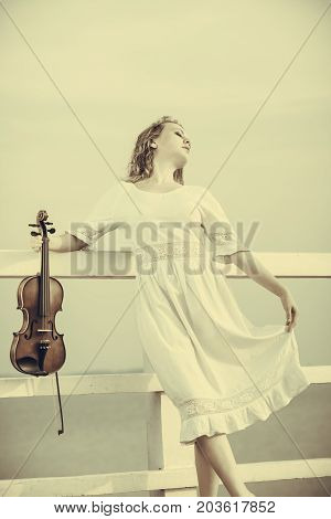 Woman On Pier Outside Holding Violin