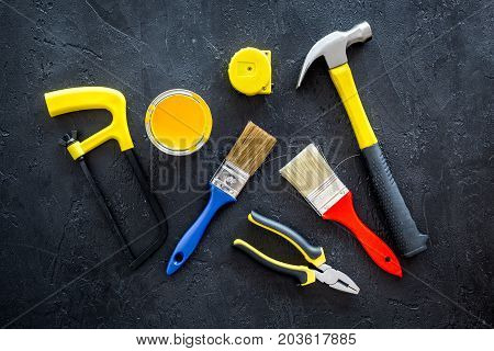 constructor desk with set of building implements and brushes on dark desk background top view
