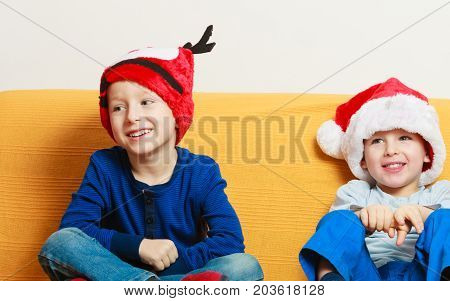 Christmassy decorations and accessories concept. Two little boys on sofa wearing christmas hats