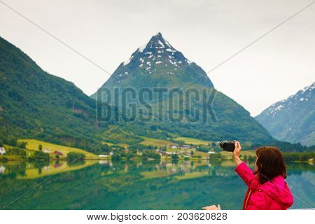 Tourism and travel. Woman tourist taking photo with camera enjoying fjord mountains view Sogn og Fjordane county. Norway Scandinavia.