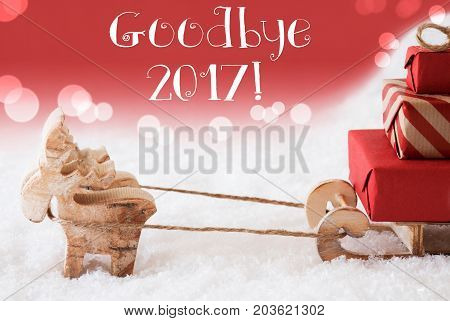 Moose Is Drawing A Sled With Red Gifts Or Presents In Snow. Christmas Card For Seasons Greetings. Red Christmassy Background With Bokeh Effect. English Text Goodbye 2017 For Happy New Year