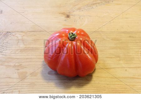 Single red heirloom tomato aligned lower center, horizontal aspect