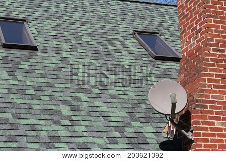 Satellite dish on green roof with skylights, horizontal aspect