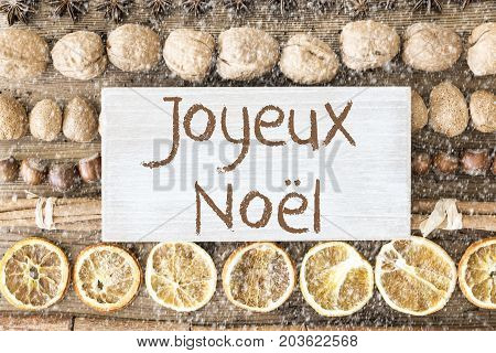 Sign With French Text Joyeux Noel Means Merry Christmas. Christmas Food Flat Lay With Walnut, Hazelnut, Cinnamon Sticks And Orange Peel. Brown Wooden Background With Snowflakes