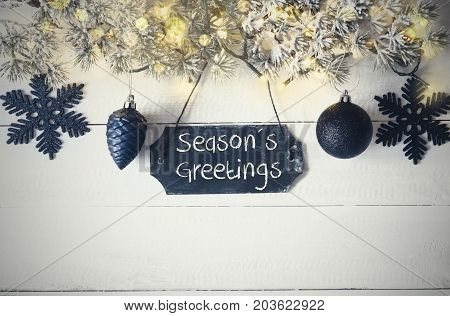 Black Chirstmas Plate With English Text Seasons Greetings. Fir Branch With Fairy Lights On Wooden Background. Black Christmas Decoration Like Balls And Snowflakes.