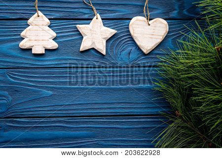 tree, heart and star toys to decorate christmas tree for new year celebration with fur tree branches on blue wooden table background top veiw mockup