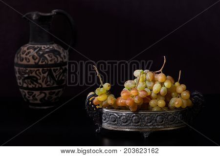 Still life with white grapes and antique pitcher on black background.