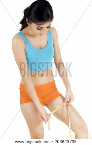 Portrait of young woman measuring her thigh with measuring tape isolated on white background