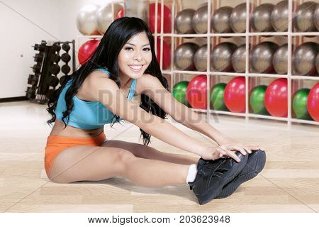 Photo of young woman looking at the camera while doing a warming up in the fitness center