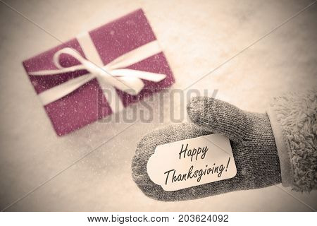 Glove With Label With English Text Happy Thanksgiving. Pink Or Rose Gift Or Present On Snow In Background. Seasonal Greeting Card With Snowflakes And Instagram Filter