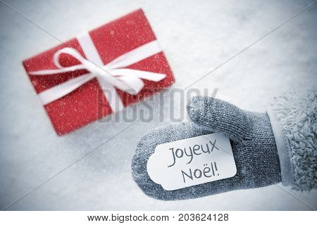 Glove With Label With French Text Joyeux Noel Means Merry Christmas. Red Gift Or Present On Snow In Background. Seasonal Greeting Card With Snowflakes.