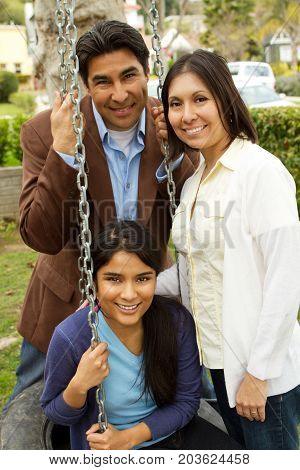 Hispanic family with a teen daughter sitting outside.