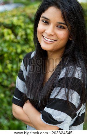 Portrait of a Hispanic teenage girl smiling outside.