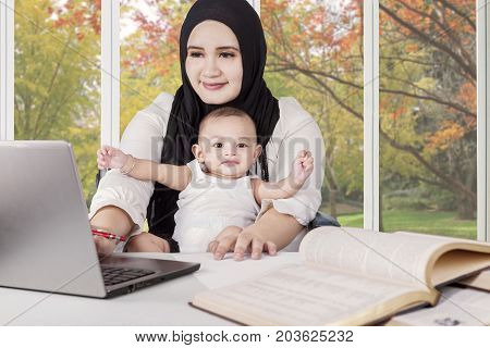 Portrait of a young muslim mother doing her job with laptop computer while taking care her baby at home