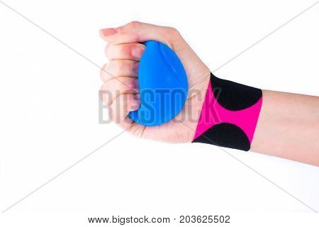 hand with kinesiology tape and stressball.  Physiotherapy and therapeutic tape for wrist pain, aches and tension. elastic therapeutic tape. adhesive tape and alternative medicine.