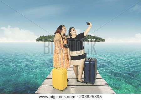 Two fat women taking a selfie photo by using smartphone while standing with a suitcase in the jetty
