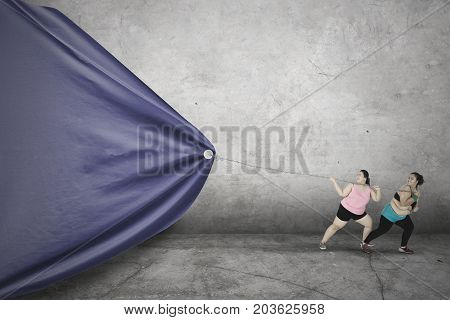 Two fat women wearing sportswear and dragging a big empty flag with a chain shot with grey wall background