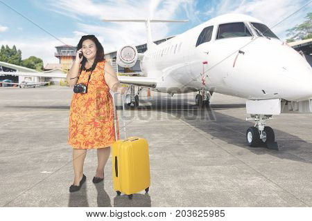 Image of fat female tourist speaking on a mobile phone while standing with a baggage in the airport