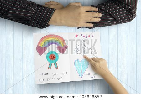 Close up of little child saying thank you to her father with greeting card on the wooden background