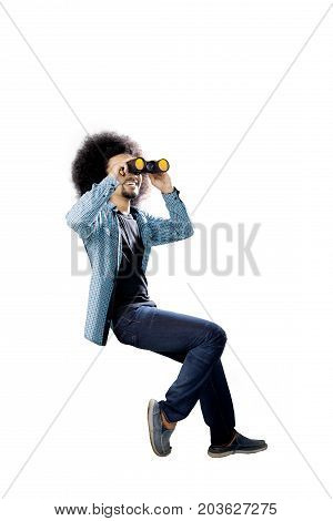 Portrait of an Afro male college student wearing casual clothes while looking through a binocular isolated on white background