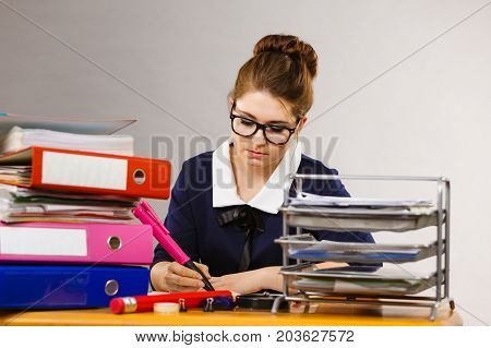 Unrecognizable woman sitting working at desk full off documents in binders writing something down