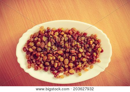 Delicacies dry fruits cake additives concept. Plate bowl full of yellow dried raisins